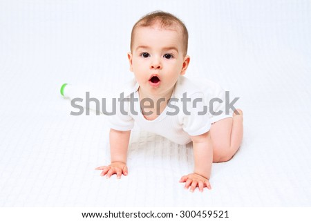 Beautiful infant child baby with bottle on a white background - stock photo