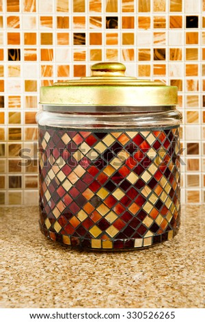 Beautiful inlaid glass jar for foodstuffs with a brass lid stand on the kitchen table - stock photo