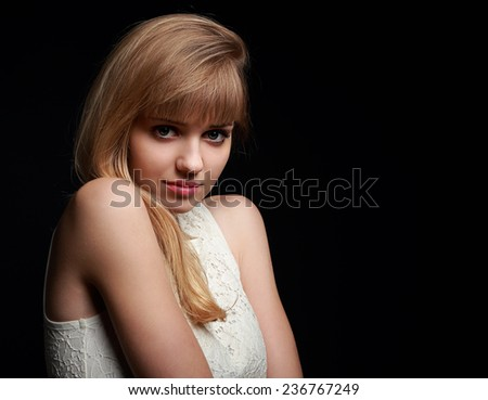 Beautiful innocence blond woman posing on black background - stock photo