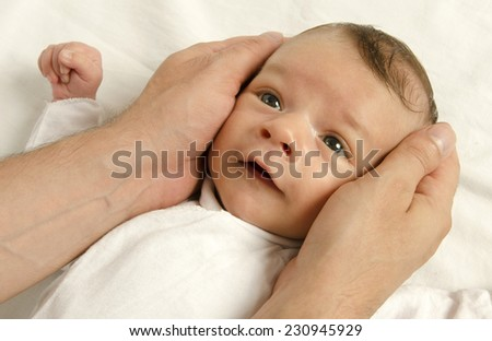 Beautiful innocent newborn looking at his father. Adorable little boy relaxing in white sheets after a bath, father's hands holding his newborn with love - stock photo