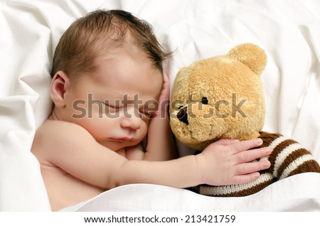Beautiful innocent newborn sleeping. Adorable little boy relaxing in white sheets after a bath and holding close to him his bear toy - stock photo