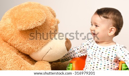 Beautiful innocent newborn speaking with his best friend, teddy bear. Adorable baby playing, having fun with his bear toy. Little sweet kid talking and listening his toy - stock photo