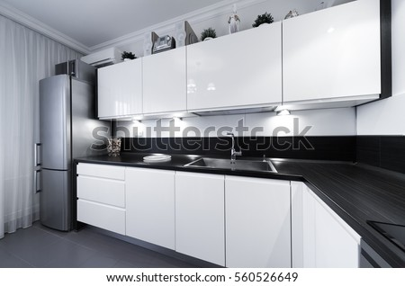 Beautiful interior apartment kitchen. Classic style. Design background. Home decoration. Nature materials. White, gray, black color. Stoneware tiles floor.