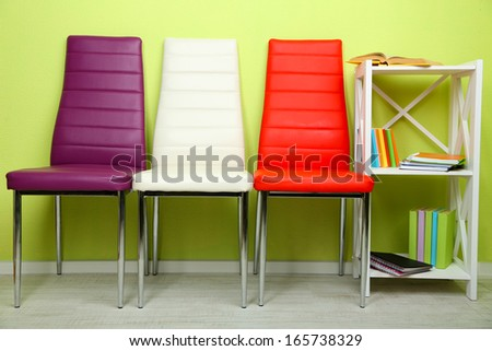 Beautiful interior with modern  color chairs,  books on wooden stand, on wall background