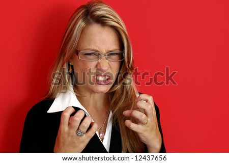 Beautiful irate woman on the red background - stock photo