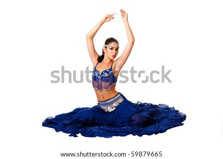 Beautiful Israeli Egyptian Lebanese Middle Eastern belly dancer performer in blue skirt and bra with arms in air sitting, isolated. - stock photo