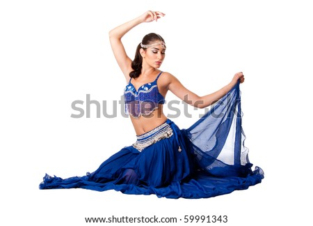 Beautiful Israeli Egyptian Lebanese Middle Eastern belly dancer performer in blue skirt and bra with arm in air sitting with eyes closed, isolated. - stock photo