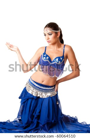 Beautiful Israeli Egyptian Lebanese Middle Eastern fashion belly dancer performer in blue skirt and bra sitting on knees, isolated. - stock photo