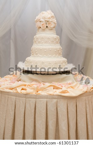 Beautiful ivory wedding cake with pink roses on a table - stock photo