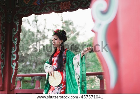 Beautiful Japanese Chinese woman in kimono national posing in the park garden, spring summer, Asia, on a background of oriental architecture with fan in her hands graceful, exotic - stock photo