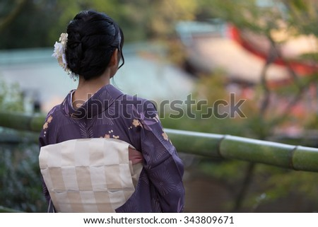 Beautiful Japanese girl in a seasonal kimono looking at a scene of a traditional Japanese garden during autumn - stock photo