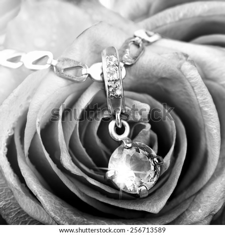 Beautiful jewelery - gold pendant with big topaz and diamonds on rose petals, black and white - stock photo