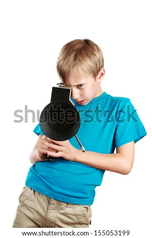 Beautiful joyful blond boy in a blue t-shirt holds a vintage motion picture camera shooting a film  - stock photo