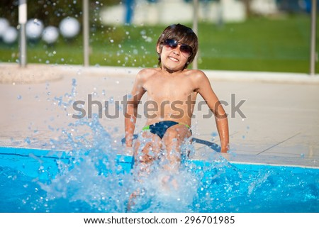 Beautiful joyful boy in sunglasses and bathing trunks sitting on the edge of the pool and splash water summer day on vacation