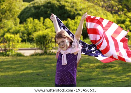 Beautiful joyful girl in a white dress holding a large American flag