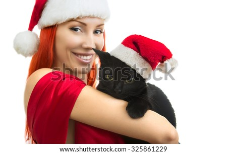 Beautiful Joyful Sexy Smiling Woman in Red Santa Claus Hat with Funny Black Cat Santa - Cute Christmas Cat, Christmas pet with Santa Claus hat. Isolated on white. Happy Christmas and New Year Holidays - stock photo