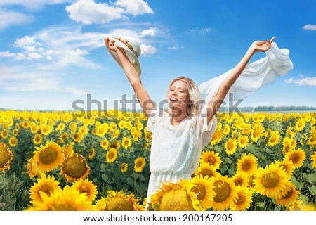 Beautiful joyful woman in blooming sunflower field