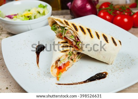 Beautiful juicy kebab in lavash with meat and vegetables. Doner kebab. Kebab - grilled meat and vegetables - stock photo