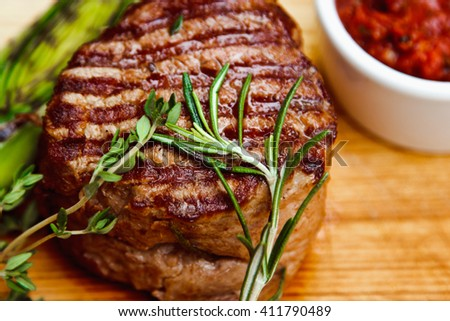 Beautiful juicy well done steak with sauce on a wooden Board - stock photo