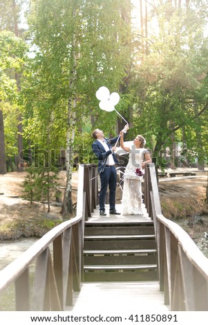 Beautiful just married couple holding white balloons on wooden bridge - stock photo