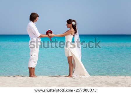 Beautiful just married couple on the beach with white sand and  blue sea  - stock photo