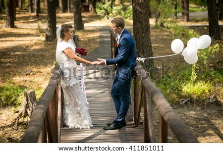 Beautiful just married couple posing on old wooden bridge with white balloons - stock photo