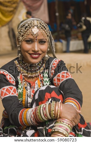 Beautiful Kalbelia dancer in ornate black costume trimmed with beads and sequins at the Sarujkund Fair near Delhi in India. - stock photo