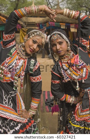 Beautiful Kalbelia dancers in ornate black costumes trimmed with beads and sequins at the annual Sarujkund Fair near Delhi, India.
