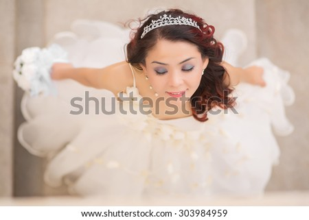 Beautiful kazakh woman bride in white wedding dress view from above - stock photo