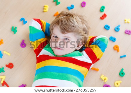 Beautiful kid boy having fun with lots of colorful plastic digits or numbers, indoor. Child wearing colorful shirt and  learning math - stock photo