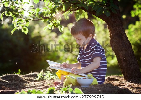 Beautiful kid boy, reading a book in garden, sitting next to a tree, gorgeous sunset light - stock photo