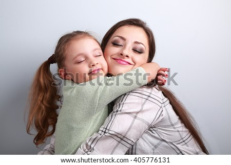 Beautiful kid girl and mother hugging with closed true enjoying eyes on blue background