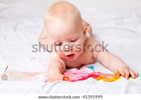 Beautiful kid lying on bed and painting - stock photo