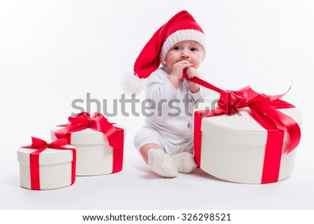 beautiful kid sitting in a New Year's cap and white body among Christmas boxes with gifts and unpacks gift, Photo with depth of field