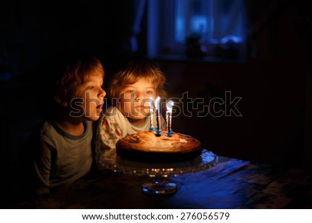Beautiful kids, little boys celebrating  birthday and blowing candles on homemade baked cake, indoor. Birthday party for children. Happy twins. - stock photo