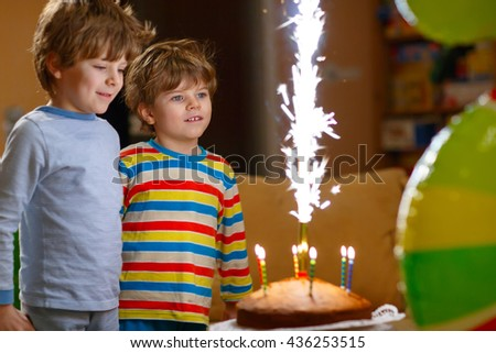 Beautiful kids, little boys celebrating birthday and blowing candles on homemade baked cake, indoor. Birthday party for children. Happy twins about fireworks - stock photo