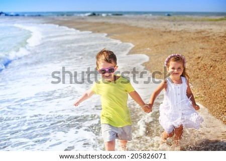 beautiful kids running along the beach. happiness, relax, wind, waves
