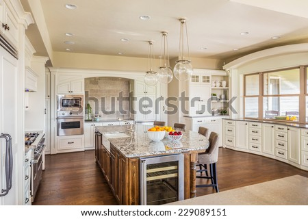 Beautiful Kitchen in Luxury Home with Island, Hardwood Floors, and Elegant Cabinetry - stock photo