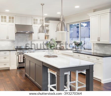 Beautiful Kitchen In Luxury Home With Island, Pendant Lights, Cabinets, And  Hardwood Floors