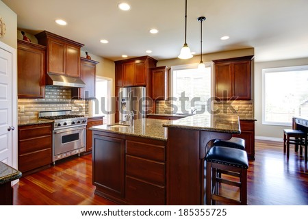 Beautiful kitchen room with oak cabinets, steel appliances. View bar counter with black chairs. - stock photo