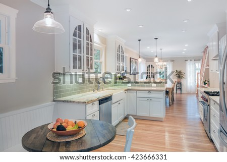 Beautiful kitchen with breakfast table, white marble counter tops, wooden floor, french doors and stainless steel appliances.  - stock photo