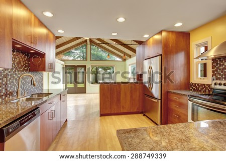 Beautiful kitchen with marble  counters and hardwood floor. Natural vaulted wood ceiling. Cherry kitchen with open floor plan.