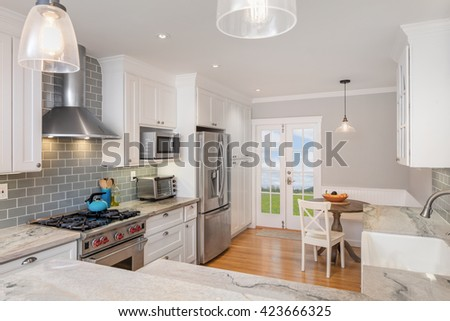Beautiful kitchen with white marble counter tops, wooden floor, french doors and stainless steel appliances.  - stock photo