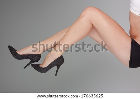 beautiful ladies shapely legs from the waist down posing in black panties and high-heeled shoes - stock photo
