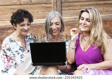 beautiful ladies smile looking at something on the laptop - stock photo