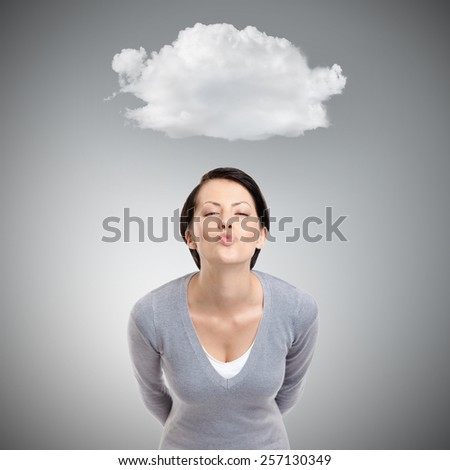 Beautiful lady blows a kiss, isolated on grey background with cloud - stock photo