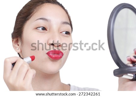 Beautiful lady checking her lips with lipstick in a mirror. Isolated in white background. - stock photo