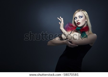 Beautiful lady dancing tango on a dark background - stock photo