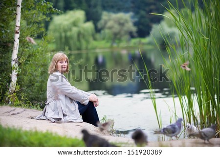 Beautiful lady feeding pigeons on a lake shore in autumn