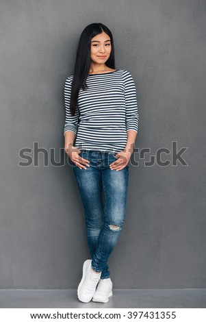 Beautiful lady. Full length of beautiful young Asian woman keeping hands in pockets and looking at camera with smile while standing against grey background - stock photo